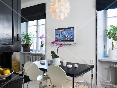 A black dining table with white Bauhaus chairs and a TV on the wall