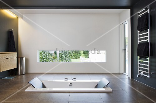 A sunken bathtub in a designer bathroom with a window opening and indirect lighting