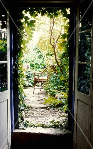 View through an open terrace door of a lush garden