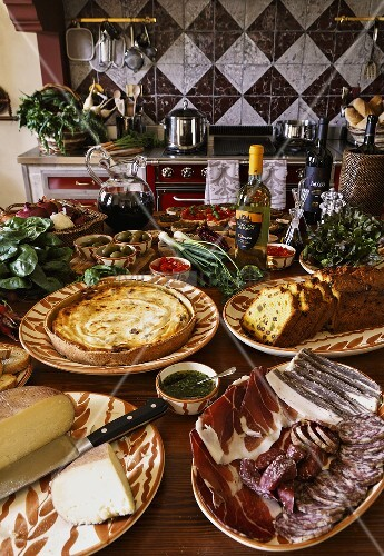 A lavishly decorated table set with starters and a meat platter