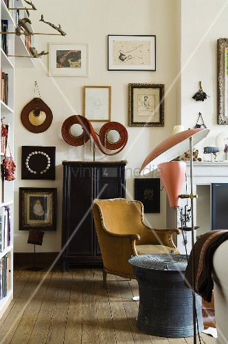 A corner of a living room in a period building - a mix of furniture styles and a collection of pictures on the wall