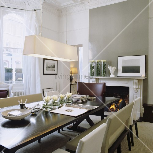 An Art Deco dining area with a pendant lamp with a white shade in front of a grey-painted wall with a fireplace
