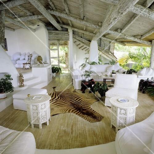 rustikale holzdecke im tropischem einraumhaus mit offenen ausblicken und tierfell auf dem. Black Bedroom Furniture Sets. Home Design Ideas