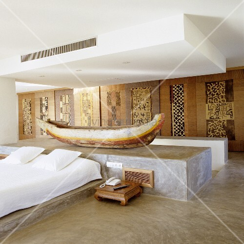 A Mediterranean bedroom with a boat displayed on a concrete pedestal