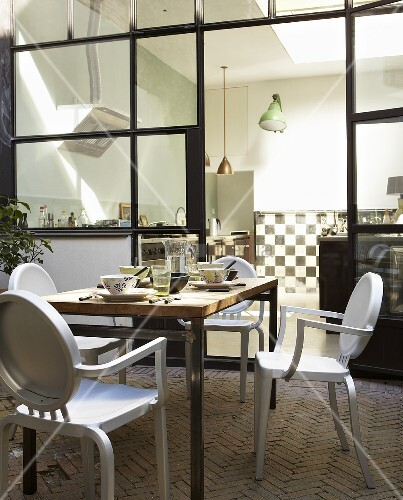 Breakfast on a roof terrace - a laid table with a view into the kitchen