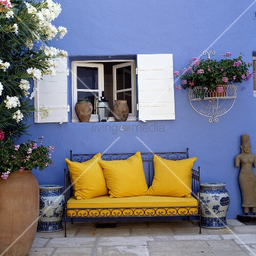 Yellow sofa cushions on a decorative metal frame in front of a blue wall