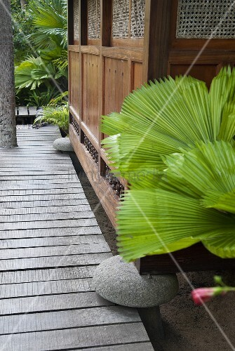 A garden path at the side of an Asian-style wooden hut standing on rocks