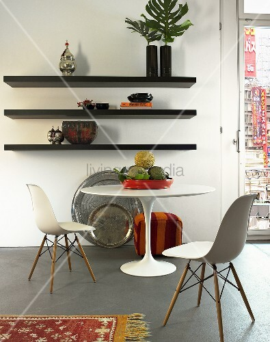Baushaus-style white table and chairs in front of a black wall shelf