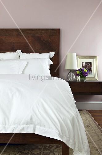 Schlafzimmer mit Doppelbett, Bettkopfteil in Holzausführung & Nachttisch mit Leuchte & Bilderrahmen (Ausschnitt)