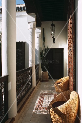 A balcony of a Moroccan house with wicker chairs and cactus