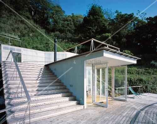 neubauhaus mit eingang und offenen t ren vor holzterrasse und treppe aus holz bild kaufen. Black Bedroom Furniture Sets. Home Design Ideas
