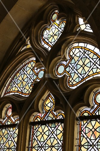 A colourful stained glass window in a Gothic pointed arch