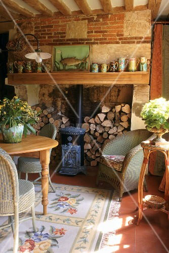 Wood stacked in a fireplace and wicker chairs in a living room of an old country house