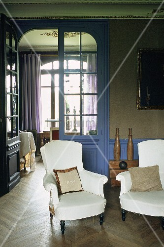 An art nouveau style living room - white upholstered armchairs in front of a floor-to-ceiling glass door with a view into the next room