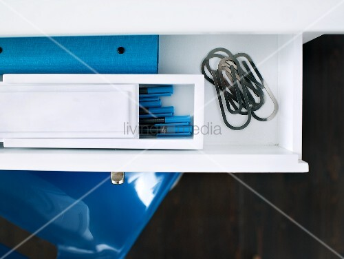 Pens in a white box and paper clips on a console