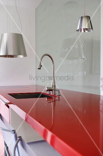 Spüle und Armatur in roter Arbeitsplatte aus Kunststoff und ...
