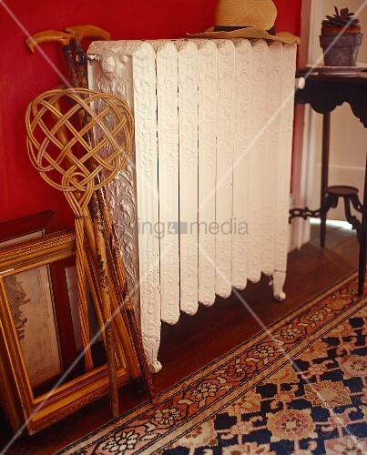 A carpet beater and a picture frame next to an antique radiator against a red wall