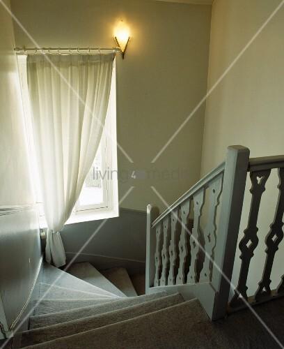 Brennende Wandlampe und Gardine vor Fenster in gewendeltem