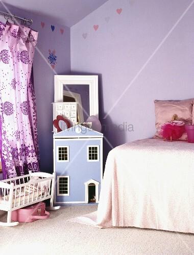 Blaues Puppenhaus und lila Vorhänge im lila Schlafzimmer – Bild kaufen – living4media