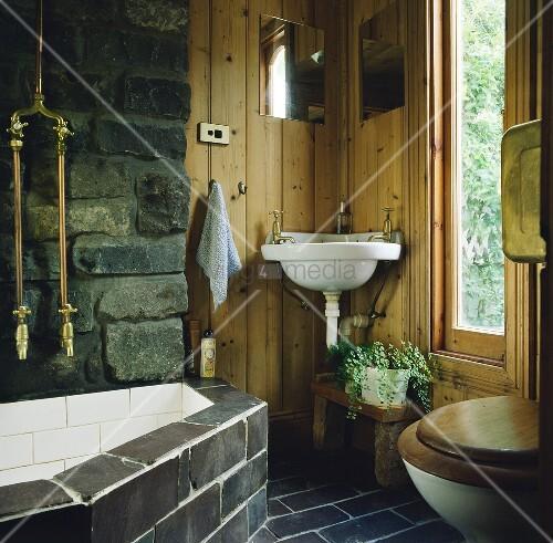 Ein schwarzer Fliesenboden umgibt ein rustikales Badezimmer mit ...