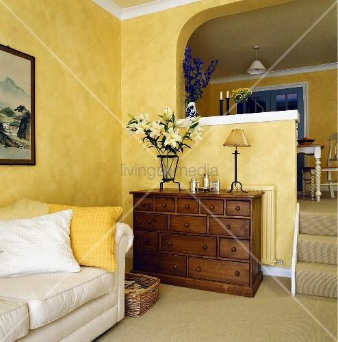 ein gelbes wohnzimmer mit einem wei en sofa und einer kommode bild kaufen living4media. Black Bedroom Furniture Sets. Home Design Ideas