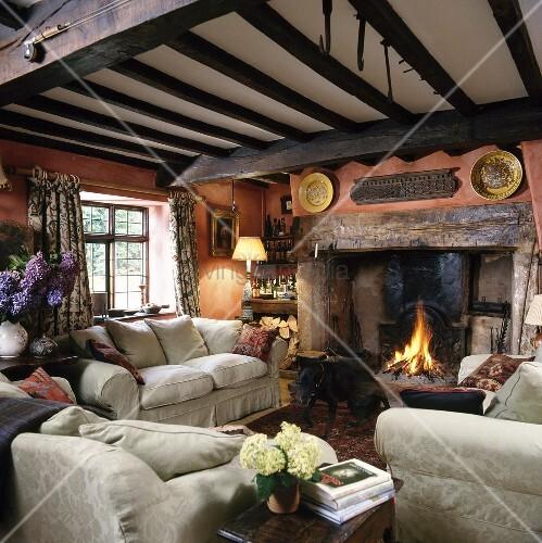 Rustikale Kamine helles sofas im rustikalen ferienhaus mit balkendecke und feuer im