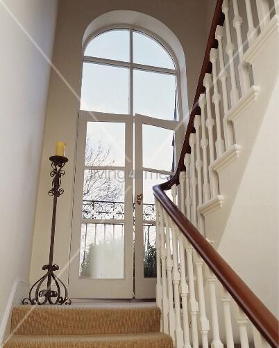 traditionelles treppenhaus mit bodenkerzenst nder aus metall neben franz sischem fenster bild. Black Bedroom Furniture Sets. Home Design Ideas
