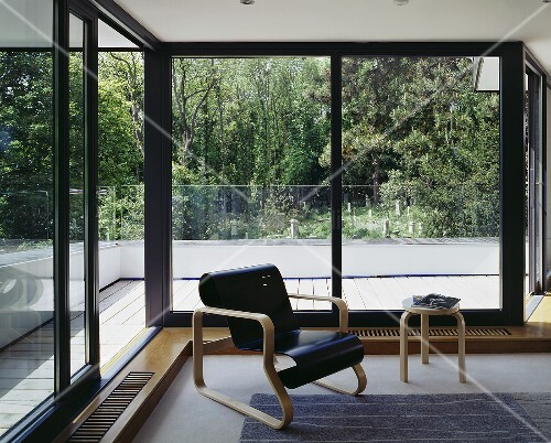 A Bauhaus armchair with a curved, black-painted seat in front of terrace doors